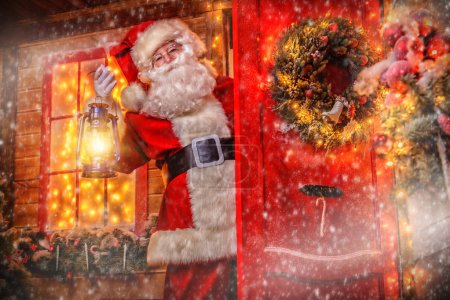 Photo for Christmas concept. Portrait of a fairytale Santa Claus peek out from behind the door with lantern and wonders. Beautiful house decorated for Christmas. Time of miracles. - Royalty Free Image