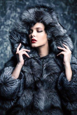 Photo pour Beautiful woman in a fur coat with hood posing in studio. Luxury, rich lifestyle. Fashion shot. - image libre de droit