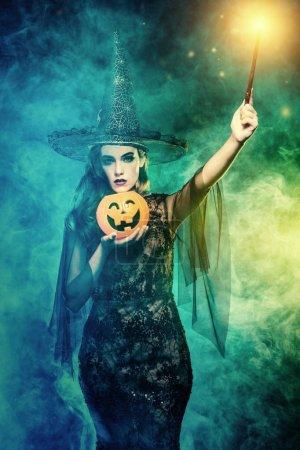 Photo pour Une sorcière tenant un bâton magique et une citrouille. Halloween. Célébration. - image libre de droit