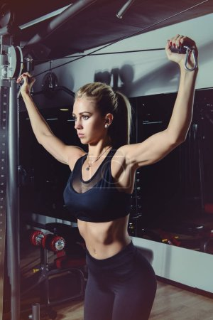 Beautiful athletic young woman working out in a gy...