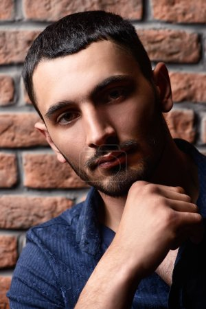 Photo for Close-up portrait of a handsome brunet man over brick wall background. Men's beauty, fashion. Men's barbershop, Hairstyle. - Royalty Free Image