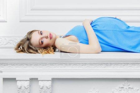 Photo pour Jeune femme enceinte en robe bleue sur fond blanc. Grossesse et maternité. Mode pour les femmes enceintes . - image libre de droit