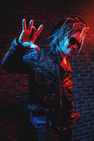 Photo pour Portrait d'un disco fou avec des dreadlocks. Fête, discothèque. Lumière colorée . - image libre de droit