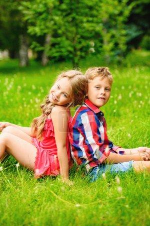 Photo pour Les enfants sont assis sur l'herbe dans la campagne. Mode, beauté. Été . - image libre de droit