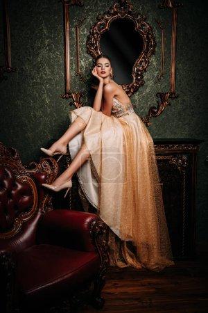 Photo pour Un portrait de toute la longueur d'une mystérieuse dame vêtue d'une robe longue moelleux, posant à l'intérieur. Intérieur, mode. - image libre de droit