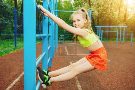 Photo for A full length portrait of a sporty teenager girl posing on the sports ground. Sport fashion, active lifestyle. - Royalty Free Image