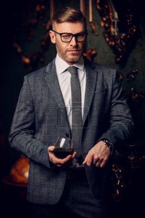 Photo pour Portrait d'un bel homme mûr en costume officiel buvant du vin. Beauté masculine, mode . - image libre de droit