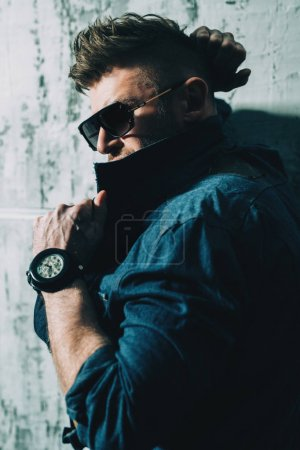 Photo pour Portrait d'un bel homme mûr brutal posant en studio au-dessus du mur gris. Mode denim décontracté, beauté masculine . - image libre de droit