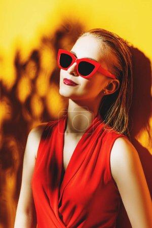 Foto de Retrato de una joven alegre posando en gafas de sol sobre el fondo con sombras de palmas. Verano, belleza . - Imagen libre de derechos