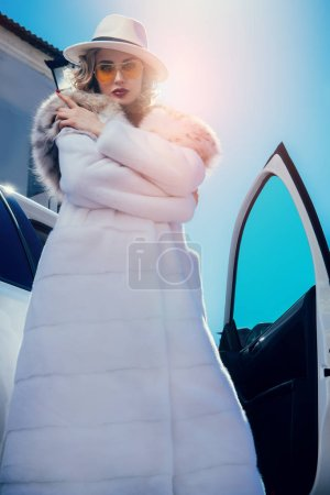 A portrait of a gorgeous blonde lady posing near a...