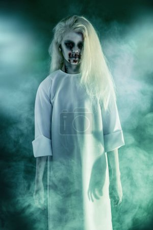 Photo pour Portrait d'une fille pâle effrayante d'un film d'horreur dans un brouillard. Zombie, Halloween . - image libre de droit
