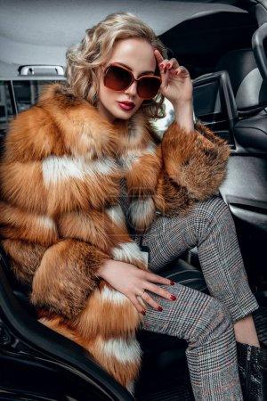 Photo pour Portrait d'une magnifique femme blonde portant des lunettes de soleil et posant dans une voiture. Voiture, mode, beauté, optique, poussin . - image libre de droit