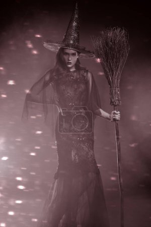 A beautiful lady in a costume of witch holding a b...