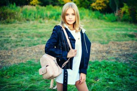 Photo pour Une belle jeune fille avec un sac à dos dans la campagne. Mode d'automne, beauté . - image libre de droit