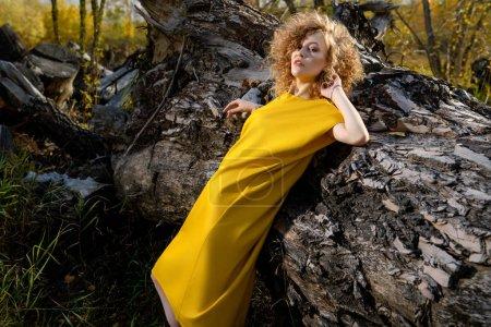 Photo pour Portrait d'une charmante jeune fille aux cheveux blonds bouclés dans une robe jaune. Mode, beauté. - image libre de droit