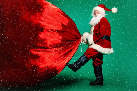 Photo for A portrait of Santa Claus with a huge gift bag. Merry Christmas and Happy New Year! - Royalty Free Image
