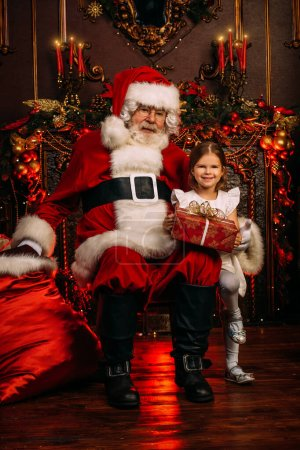 Photo for Santa Claus  and  little girl are sitting in the armchair at home with a gift bag. Merry Christmas and Happy New Year. Miracle time. - Royalty Free Image