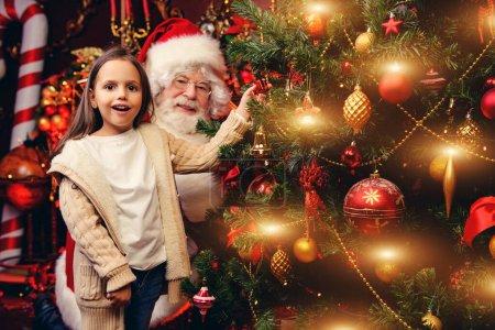 Photo pour Une jeune fille heureuse décore le sapin de Noël avec le Père Noël à la maison. Joyeux Noël et bonne année . - image libre de droit