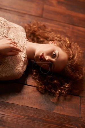 Photo pour Portrait beauté mode. Charmante jeune femme aux beaux cheveux roux bouclés se trouve sur un sol en bois. Espace de copie . - image libre de droit