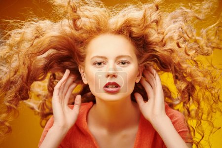 Photo for Long curly red hair. Portrait of a beautiful fashion girl with magnificent long hair in motion. Yellow background. Flying hair. - Royalty Free Image