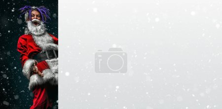 Photo for Cool punk Santa shows off clenched fists on a snow background. - Royalty Free Image