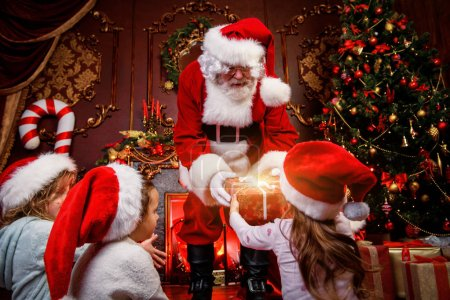 Photo for Santa Claus is giving presents to children at home. Merry Christmas and Happy New Year. Miracle time. - Royalty Free Image