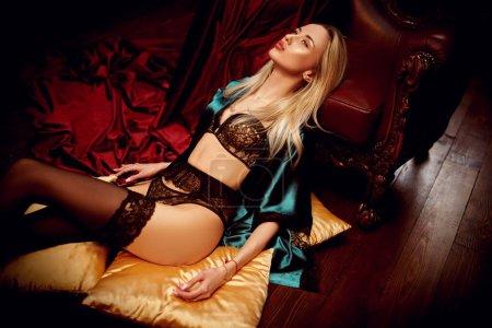 Photo pour Attractive sexy blonde salope girl in a black lace lingerie lies in a vintage armchair in a luxurious interior. Sous-vêtements mode. Concept d'amour. - image libre de droit
