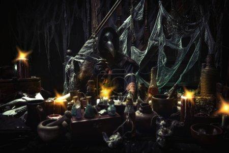Der Pestarzt arbeitet an seinem Schreibtisch und erfindet ein Heilmittel gegen Beulenpest. Die Atmosphäre der Mystik. Historische Nachstellung. Halloween.