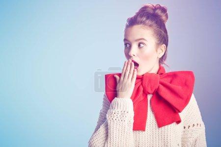 Photo pour Portrait d'une jolie fille excitée dans un pull blanc et avec un grand arc rouge élégant sur son cou contre une douce lumière rose et bleue. Beauté, concept de mode. Style d'hiver . - image libre de droit