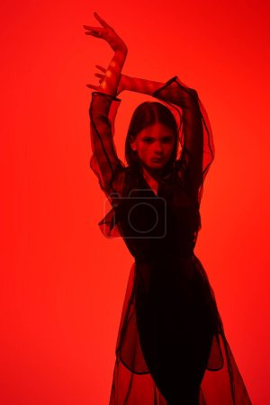 Photo for Fashion shot. Beautiful female model posing in black fashionable clothes in red light. Studio portrait. - Royalty Free Image