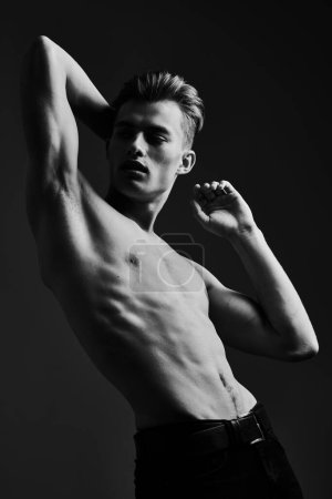 Photo for Black-and-white portrait of a handsome athletic young man with perfect muscular body. Sports and bodybuilding. Men's beauty and health. - Royalty Free Image