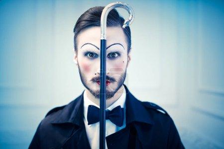 Photo pour Art et mode. Portrait d'un jeune homme maquillé dans le style des années 20 dans un costume élégant jouant différents rôles de la vie. Homme mime artiste. - image libre de droit