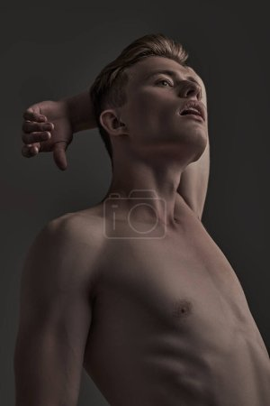 Photo for Portrait of a handsome athletic muscular man on a gray background. Man's beauty and health. Sports concept. - Royalty Free Image