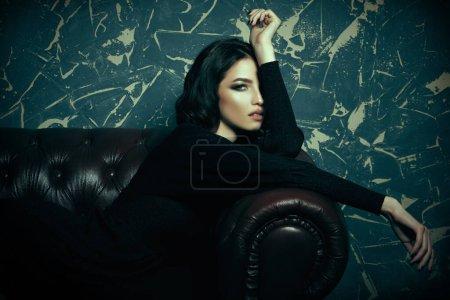 Photo pour Magnifique jeune femme brune avec maquillage du soir posant en robe noire sur un canapé en cuir. Beauté, concept de mode. - image libre de droit