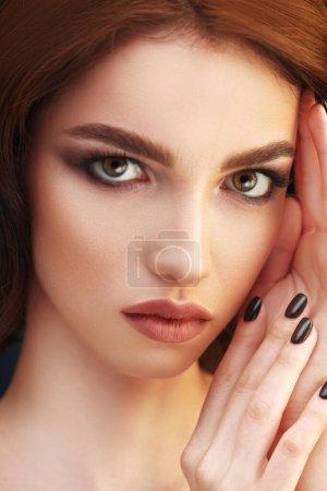 Photo pour Concept beauté. Gros plan portrait d'une belle fille regardant la caméra. Maquillage et cosmétiques, manucure. Portrait studio. - image libre de droit