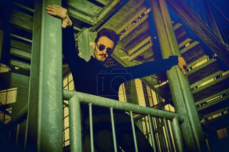 Photo for Portrait of a handsome courageous man in black clothes and black sunglasses posing on a metal industrial staircase. Urban grunge style. Male fashion. - Royalty Free Image