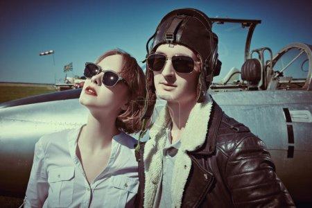 Photo pour Une belle fille et un bel homme pilotes se tiennent à côté d'un avion de combat à l'aérodrome. Avion militaire. Mode militaire. Style rétro. - image libre de droit