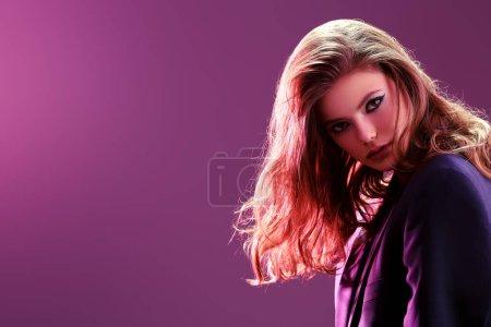 Photo pour Portrait d'une charmante fille au maquillage éclatant et aux beaux cheveux ondulés sur un fond lilas-violet. Studio portrait de beauté. Maquillage et cosmétiques. Espace de copie. - image libre de droit
