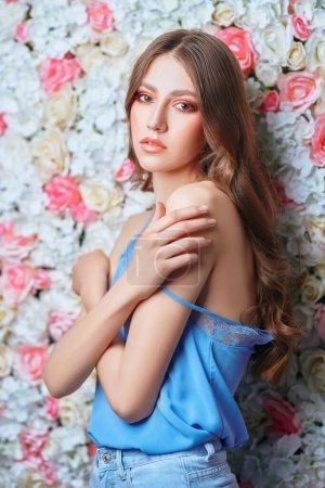Photo pour Beauté du printemps et de l'été. Portrait d'une jeune femme tendre aux longs cheveux ondulés et au maquillage coloré sur fond de roses. Maquillage et cosmétiques. - image libre de droit