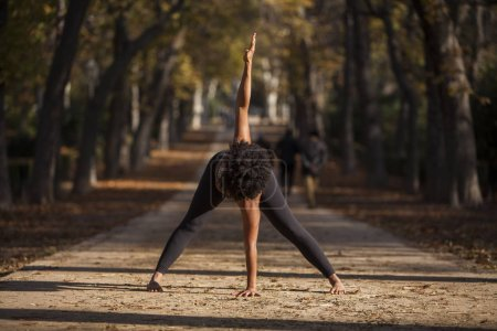 Photo for Beautiful afro woman practicing yoga outdoors, on a park path - Royalty Free Image