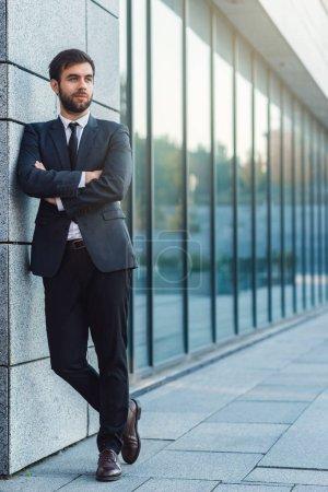 Photo pour Portrait complet de jeune homme d'affaires avec la main croisée dans un costume posant sur le fond de l'immeuble de bureaux appuyé contre le mur - image libre de droit