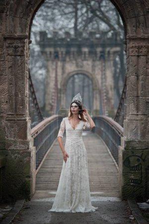 Photo pour Belle jeune femme portant une élégante robe blanche profitant des rayons de lumière céleste et des flocons de neige tombant sur son visage. Jolie fille brune en robe de mariée longue posant sur un pont dans les paysages d'hiver - image libre de droit