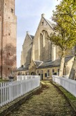 Workum, The Netherlands, November 4, 2018: footbath, lined with white fences, between the tower and the nave of Saint Gertrudis church