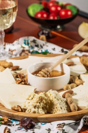 Photo for Assorted cheeses on round wooden board plate served with white wine Guda cheese, cheese grated bark of oak, hard cheese slices, walnuts, grapes, crackers, honey, sulguni, light wood background - Royalty Free Image