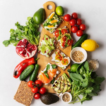 Photo for Top view of Superfood protein toast with delicious toppings on top: smoked salmon, spinach, cucumber, tomato and cream cheese on wooden long cutting board among vegetables ingredients. healthy snacks. - Royalty Free Image