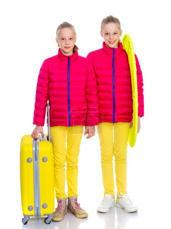 Two little girls with suitcases are traveling.