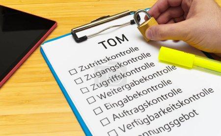 Photo pour Plaque avec l'inscription TOM Technisch organisatorische Manahmen en anglais Techniquement mesures d'organisation avec tablette et bloc pour signaler les activités typiques des délégués à la protection des données - image libre de droit