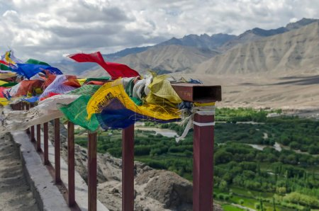 LEH, INDIA - AUGUST 4, 2017: Buddhist prayer signs in the form of multi colored flags, hangs on the rope in Himalaya, Spituk Gompa, Jamu Kasmir.