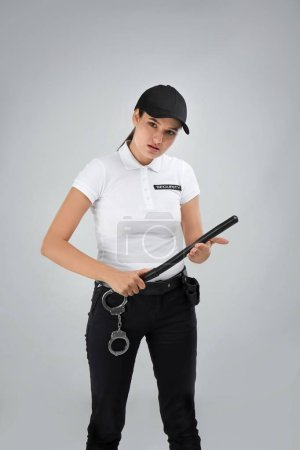 Female security guard with police baton on color background