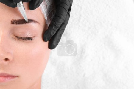 Young woman undergoing eyebrow correction procedure in salon, top view